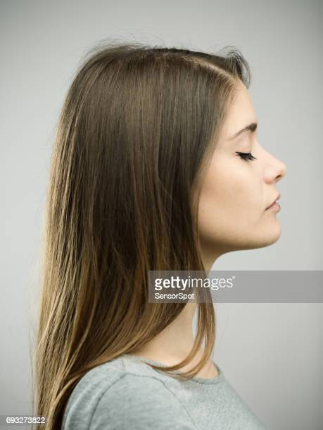 Real young woman profile studio portrait with closed eyes