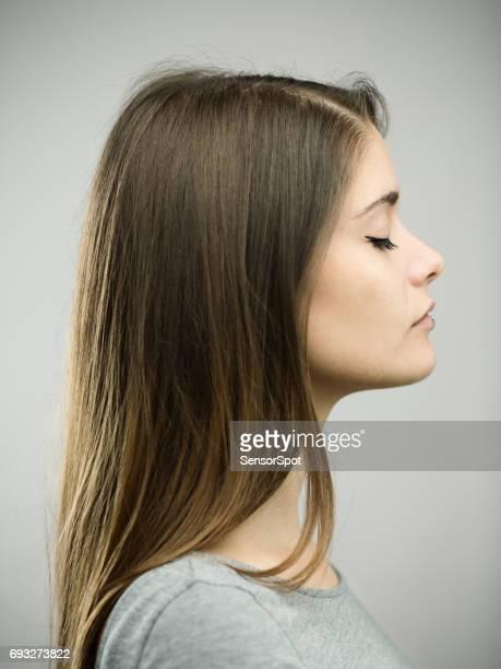 Echte jonge vrouw profiel studio portret met gesloten ogen