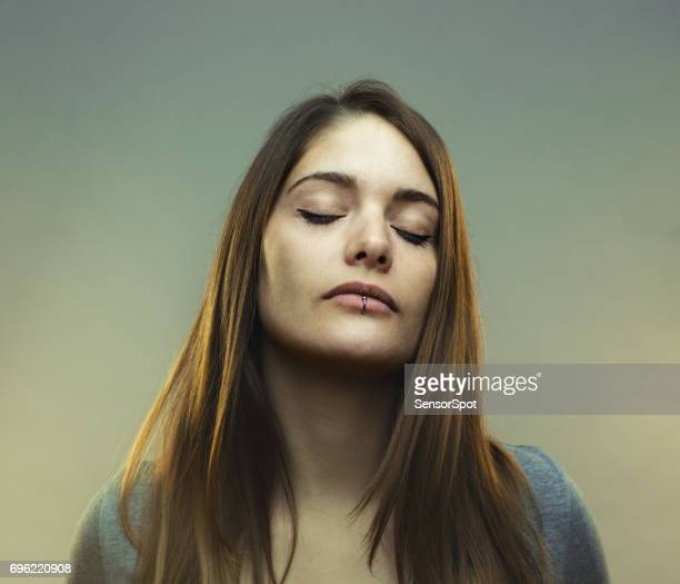 Real young woman studio portrait with closed eyes