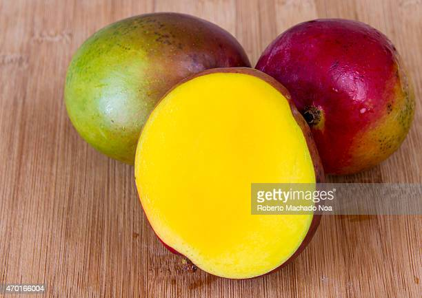 Realistic approach to food beautiful mangoes with water droplets over wooden surface or cutting board
