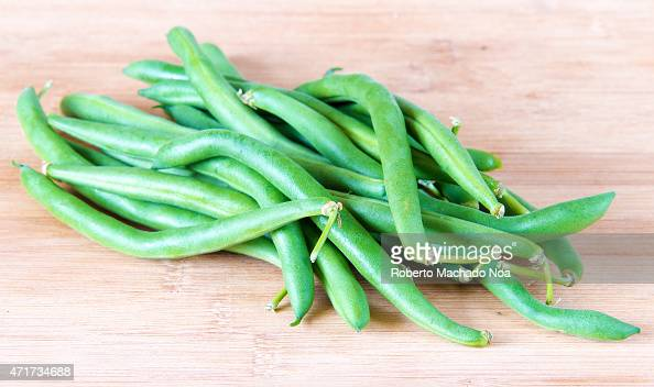 Realistic approach to food imperfect green beans sheath over wooden cutting board