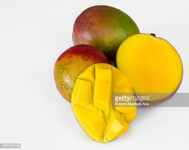 Realistic approach to tropical fruits three imperfect ripe mangos over white background not isolated