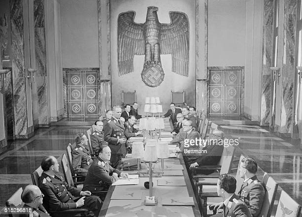 Realistically depicting a conference of Luftwaffe officials in the time of Hitler a group of German movie actors is shown in a scene from The Devil's...