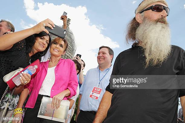 Reality television personality Phil Robertson and Sarah Palin visit with supporters during a rally against the Iran nuclear deal on the West Lawn of...