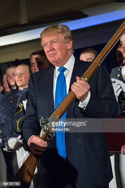 Reality TV host and New York real estate mogul Donald Trump holds up a replica flintlock rifle awarded him by cadets during the Republican Society...