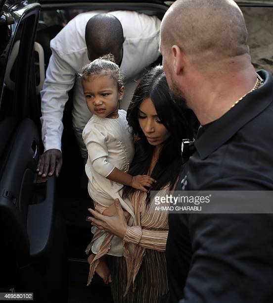 US reality TV star Kim Kardashian carries her daughter North West as she and her husband rapper Kanye West exit a car upon their arrival at the...