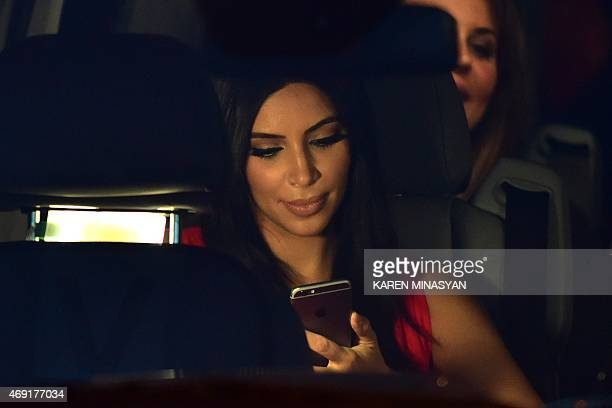 US reality TV star Kim Kardashian looks at her iPhone as she sits in a car after visiting the genocide memorial which commemorates the 1915 mass...