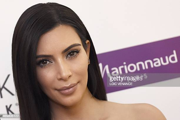 US reality TV star Kim Kardashian poses while presenting a product of her new comestic brand during a photocall on April 15 2015 in Paris AFP PHOTO /...