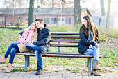 A couple of young man and woman teenagers sitting on a bench, embracing, in love and happy at the other end sits a sad alone girl