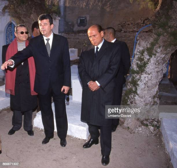 A really sad Silvio Berlusconi Tarak Ben Ammar and the Italian singer Tony Renis at the funeral chamber of the military hospital in Tunis when...