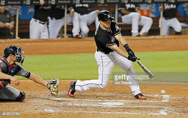 T Realmuto of the Miami Marlins hits an RBI single in the seventh inning in front catcher Anthony Recker of the Atlanta Braves at Marlins Park on...