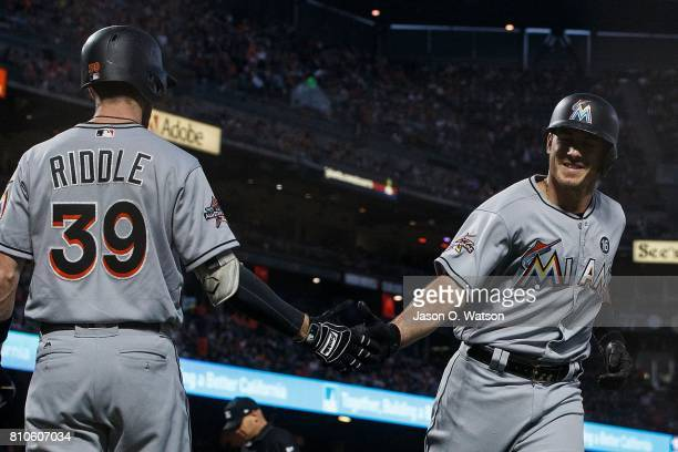 T Realmuto of the Miami Marlins is congratulated by JT Riddle after hitting a home run against the San Francisco Giants during the fifth inning at...