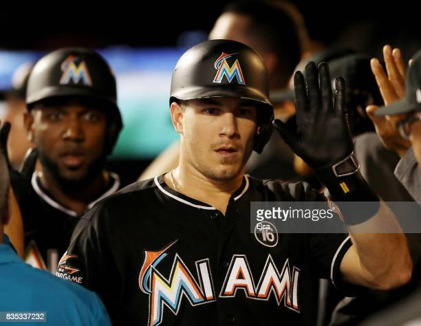 T Realmuto of the Miami Marlins is congratulated by teamamtes after he hit a two run home run scoring teammate Marcell Ozuna#13 in the second inning...