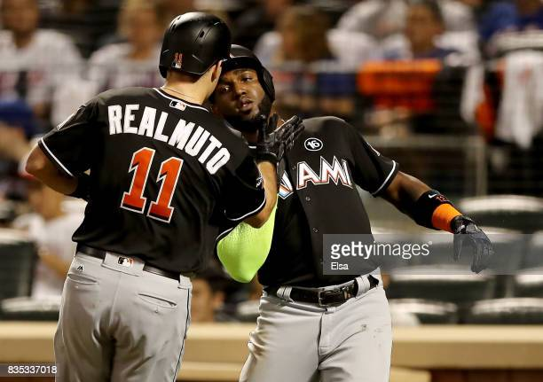 T Realmuto of the Miami Marlins is congratulated by teammatae Marcell Ozuna after he drove them both home with a two run home run in the second...