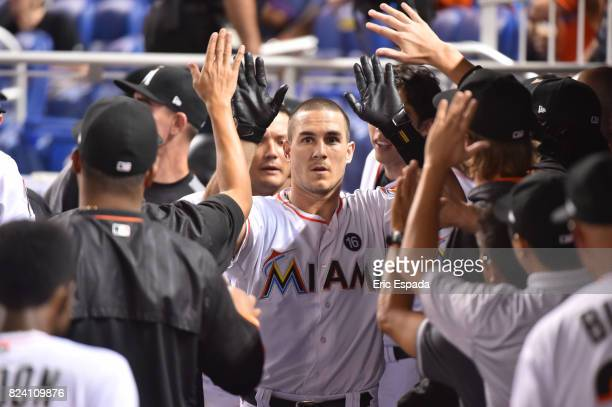 T Realmuto of the Miami Marlins is congratulated by teammates in the dugout after hitting a home run against the Cincinnati Reds at Marlins Park on...