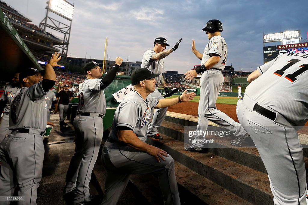 T Realmuto of the Miami Marlins is greeted in the dugout after scoring in the second inning against the Washington Nationals at Nationals Park on May...