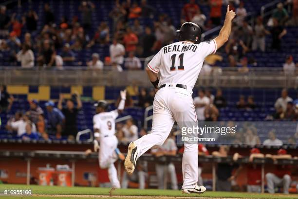 T Realmuto of the Miami Marlins scores the winning run on a bases loaded walk off single in the 11th inning by Dee Gordon during a game against the...