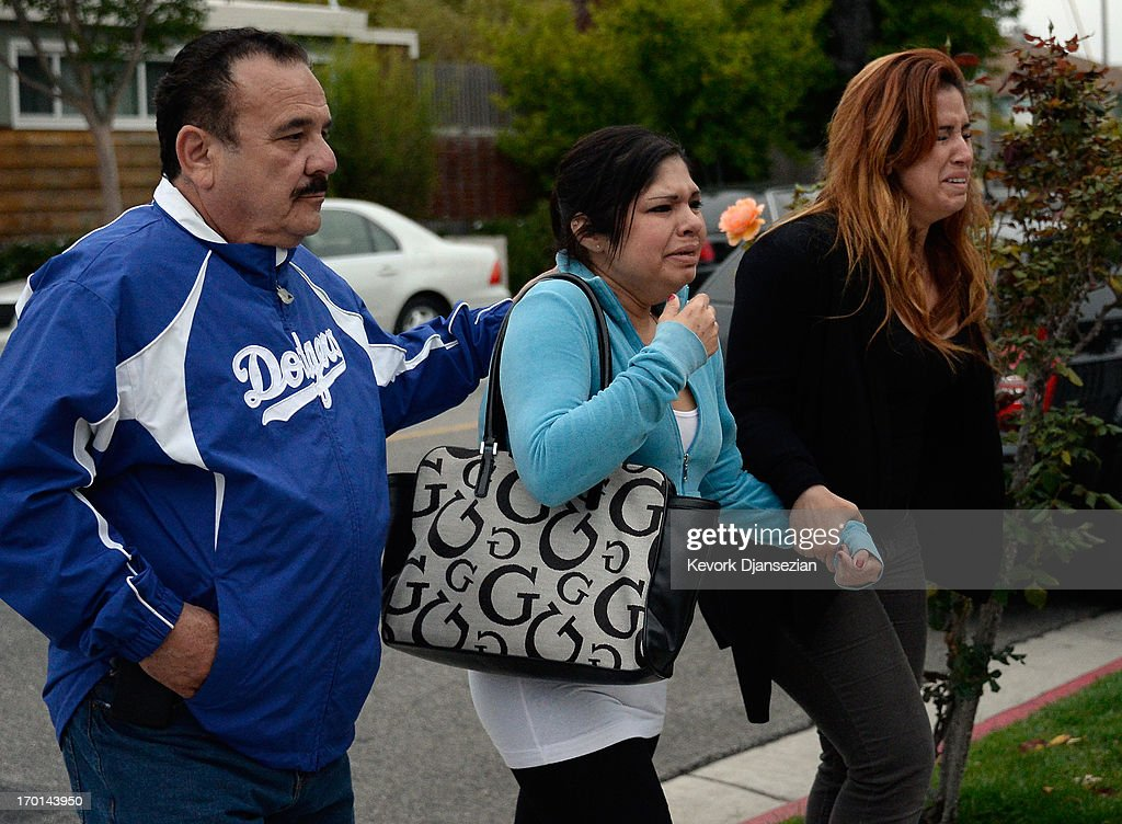 Realtives of two victims who were killed during the Santa Monica College shootings are overcome with grief near the scene where an SUV crashed throught the wall of a parking lot across the street from the college June 7, 2013 in Santa Monica, California. According to reports, seven people are dead including the shooter and three people were injured.