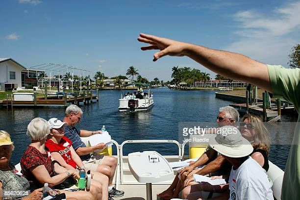 Realtor Bill Mitchell gestures as he explains some of the properties to prospective buyers taking part in a foreclosure boat tour by Foreclosures 'R...