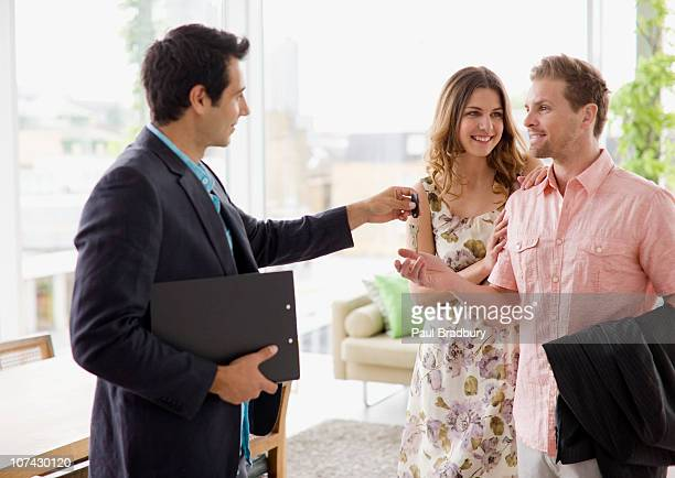 Realtor handing couple keys to home
