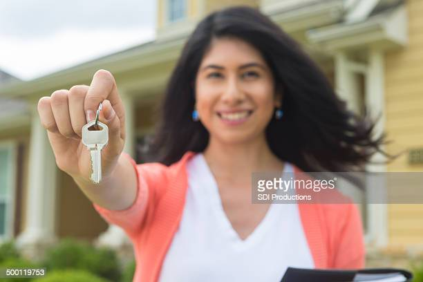 Realtor or homeowner holding key to new home; selective focus
