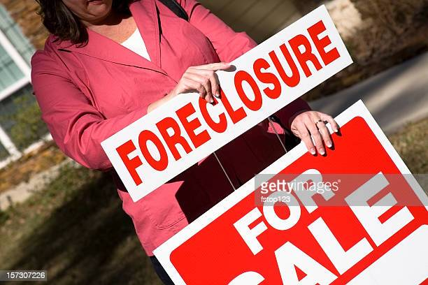 Realtor putting up Real Estate for Sale sign with foreclosure