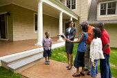 Makler zeigen Familie vor Haus zum Verkauf