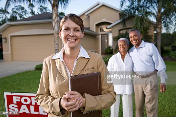 Agence immobilière avec couple afro-américain à l'extérieur de la maison à vendre