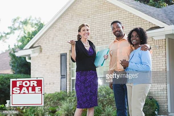 Realtor with couple in front of house for sale