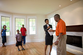 Real estate agent hands keys of house to father with the rest of the family looking on