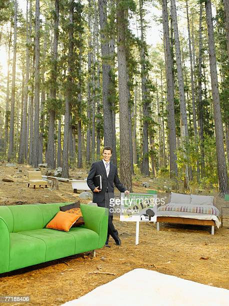 A realtor with home furnishings outdoors in the woods