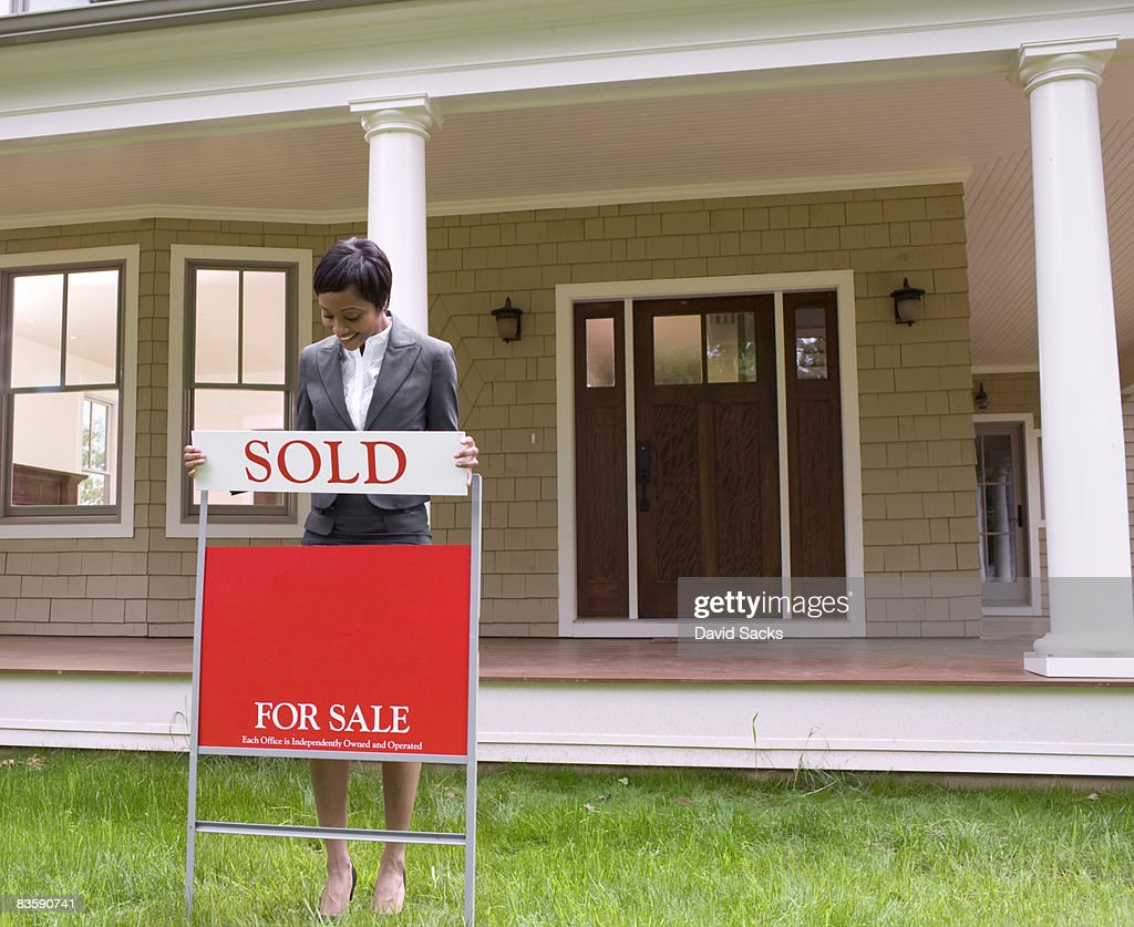 Realtor with sale sign : Stock Photo