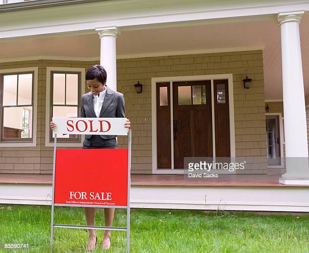 Courtier immobilier avec un signe de vente