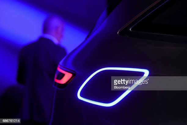 A rear light sits beside an illuminated charging point cover on a MercedesBenz Generation EQ electric sportutility vehicle manufactured by Daimler AG...
