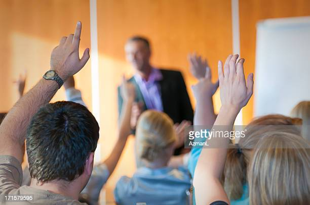 Rear of Audience Raising Hands During Seminar