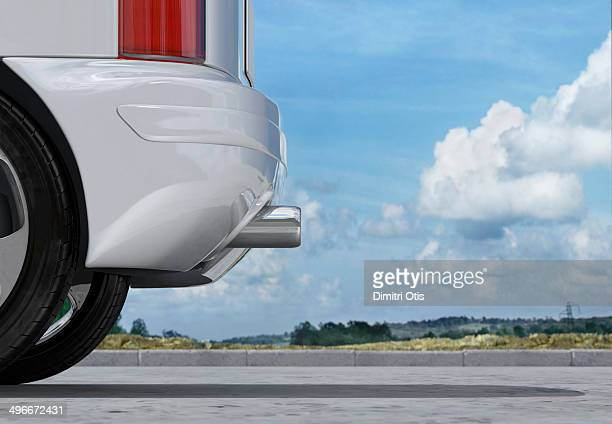 Rear of car, exhaust pipe in front of cloudy sky