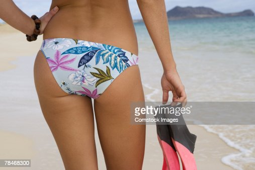 Rear of woman in bathing suit at beach holding fins : Stock Photo