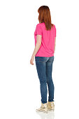 Young woman in pink t-shirt, jeans and gold sneakers is standing and looking away. Rear side view. Full length studio shot isolated on white.