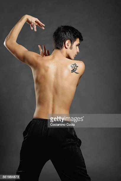 Rear studio shot of young man poised in martial arts pose