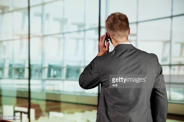 背面の眺め、携帯電話で話しているビジネスマン