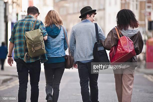 Rear view 4 friends walking in street