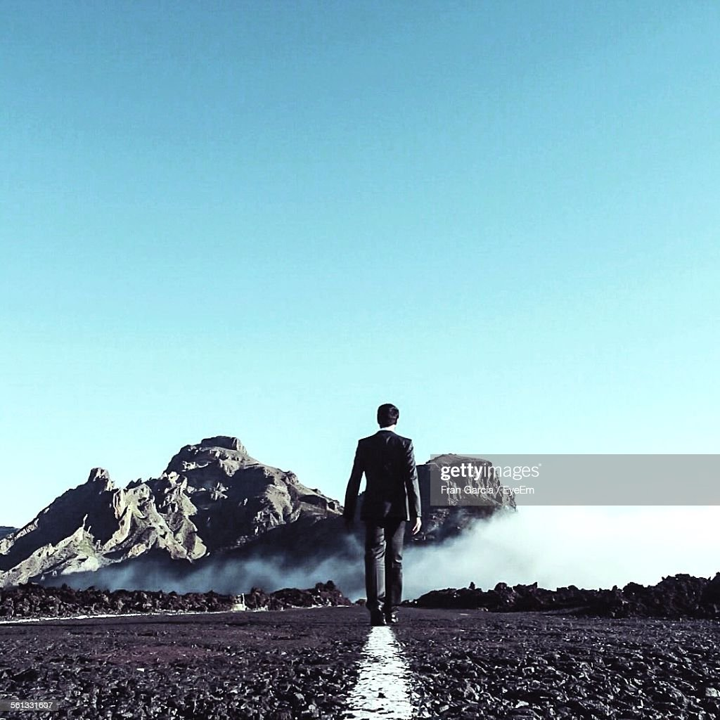 Rear View Business Man Walking On Road Against Clear Sky