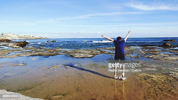 Rear View Full Length Of Boy Standing At Beach Against Sky