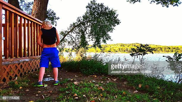 Rear View Full Length Of Boy Urinating By River