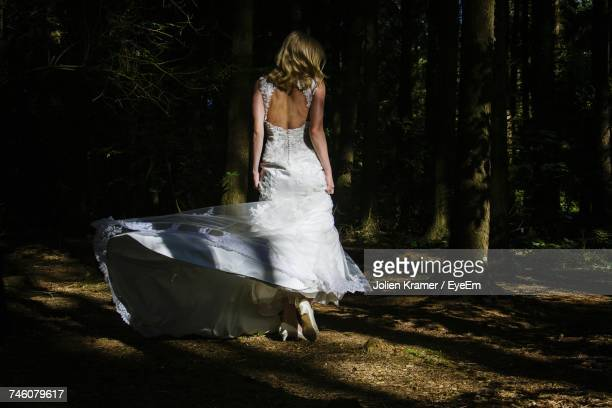 Rear View Full Length Of Bride Standing By Trees At Forest