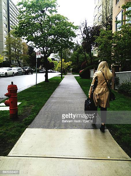 Rear View Full Length Of Businesswoman With Briefcase Walking On Footpath In City