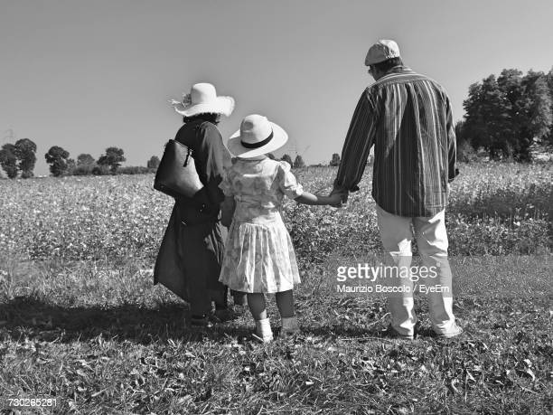 Rear View Full Length Of Family Standing On Field Against Sky