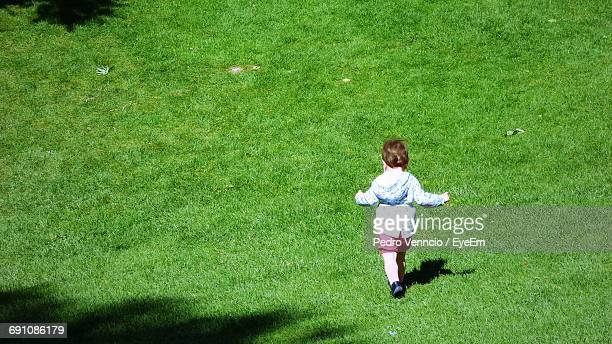 Rear View Full Length Of Girl Running On Grassy Field During Sunny Day