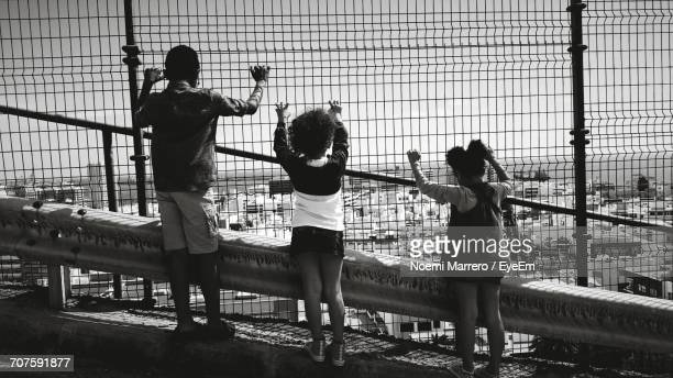 Rear View Full Length Of Siblings Looking At Townscape Through Chainlink Fence