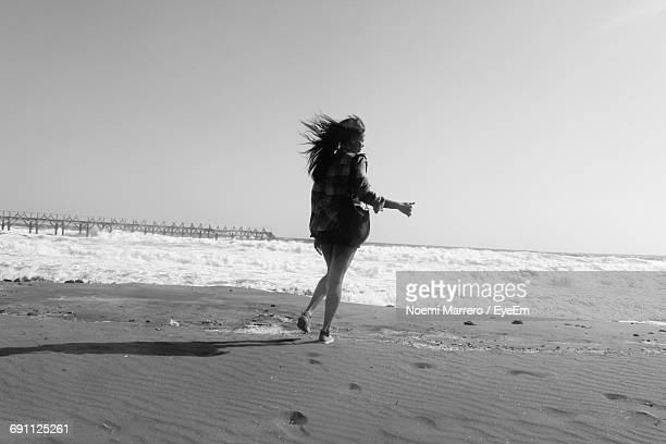 Rear View Full Length Of Woman At Beach Against Sky
